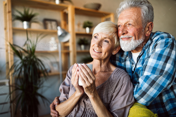 Happy romantic senior couple hugging and enjoying retirement at home - Stock Photo - Images