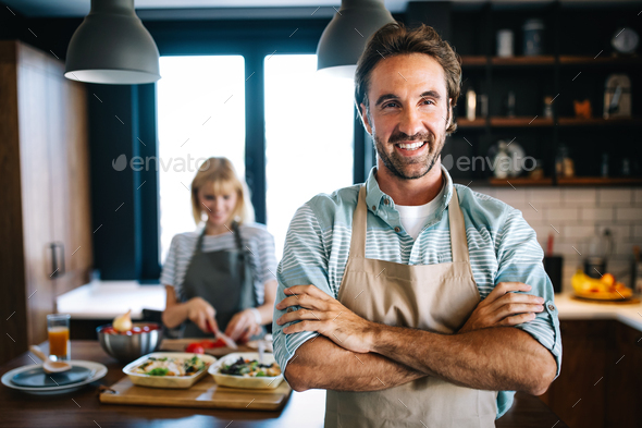 Portrait of happy young couple cooking together in the kitchen at home - Stock Photo - Images