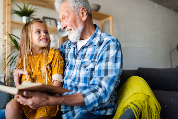 Grandfather reading book with his granddaughter at home. Happy family time - Stock Photo - Images