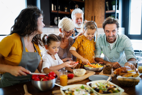 Cheerful family spending good time together while cooking in kitchen - Stock Photo - Images