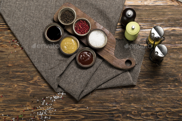 Various spices, herbs, garlic and sauces on a wooden background, studio lighting, top view - Stock Photo - Images
