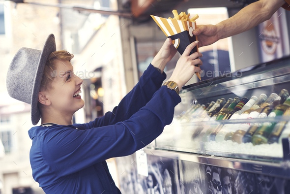 Female customer reaching food from vendor - Stock Photo - Images