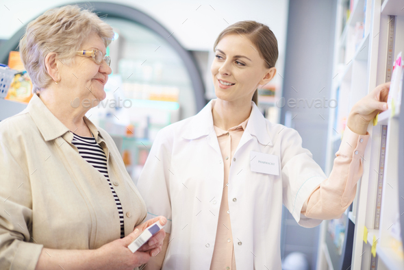 Pharmacist taking care about mature woman health - Stock Photo - Images