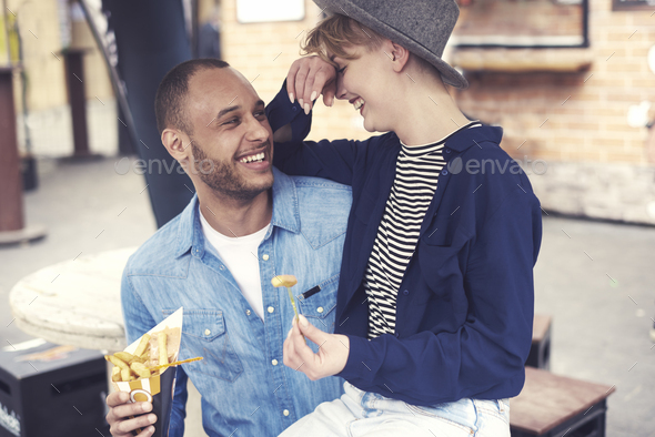 Couple eating tasty fries outdoors - Stock Photo - Images