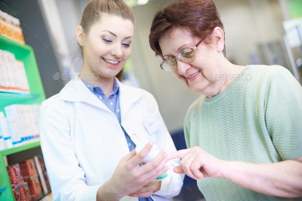 Pharmacist giving an advice senior woman - Stock Photo - Images