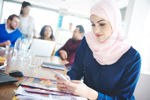 Muslim woman uing cell phone at office - Stock Photo - Images
