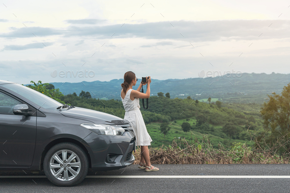 Young woman traveler taking a photo on mountain with car on roadtrip, Summer vacation - Stock Photo - Images