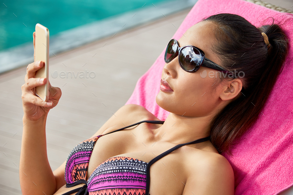 Woman resting by pool - Stock Photo - Images