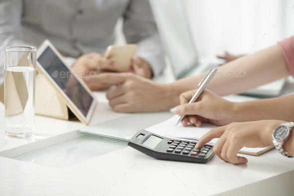 Crop woman using calculating machine - Stock Photo - Images