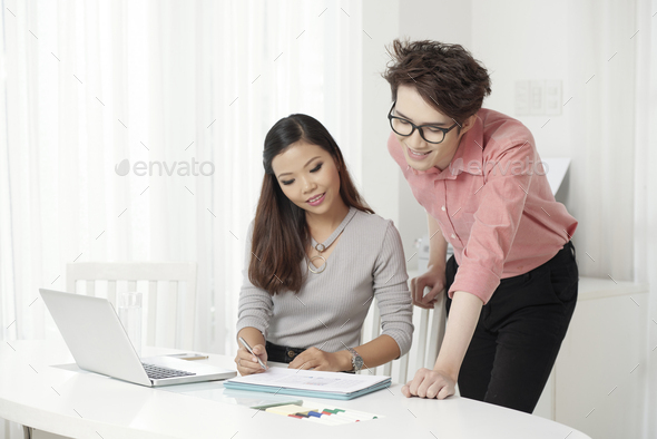 Young ethnic coworkers watching papers - Stock Photo - Images