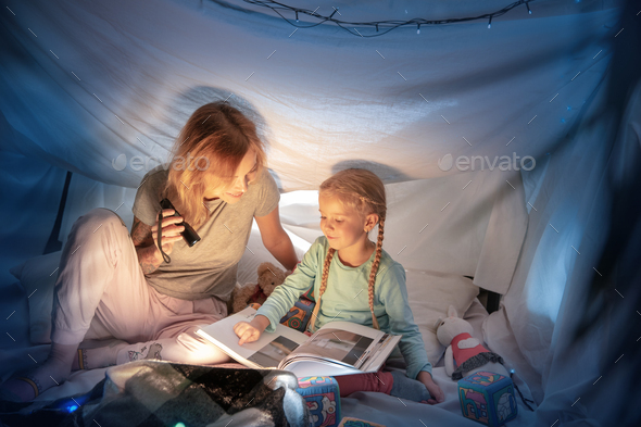 Mother and daughter sitting in a teepee, reading stories with the flashlight - Stock Photo - Images
