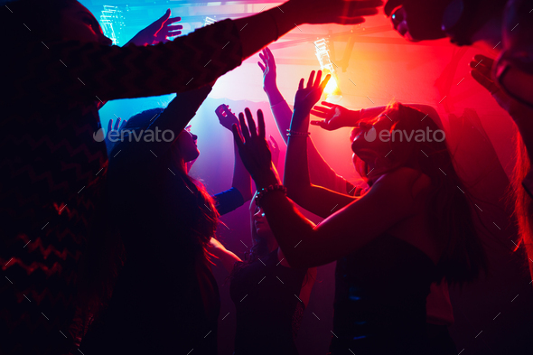 A crowd of people in silhouette raises their hands against colorful neon light on party background - Stock Photo - Images