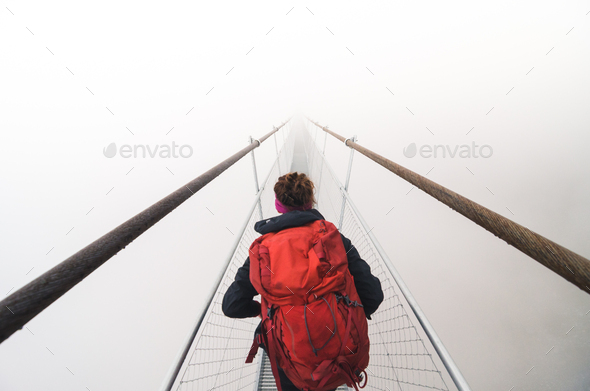 Female tourist walking across a suspension bridge in heavy fog - Stock Photo - Images