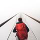 Female tourist walking across a suspension bridge in heavy fog - PhotoDune Item for Sale