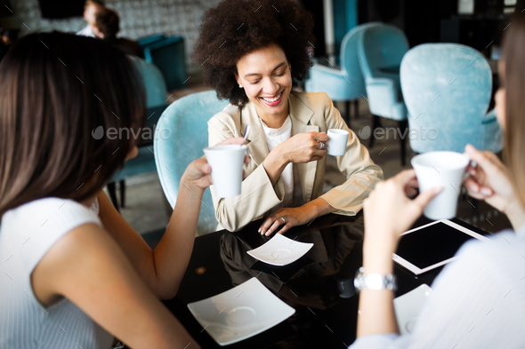 Happy laughing girls having coffee and discussing new creative project in cafe - Stock Photo - Images