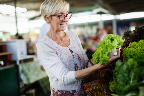 Picture of mature woman at marketplace buying vegetables - Stock Photo - Images