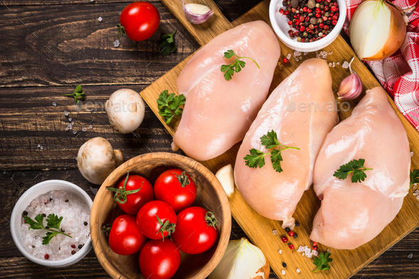 Chicken fillet with ingredients for cooking on wooden table - Stock Photo - Images