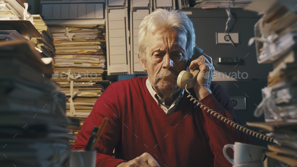 Senior businessman answering phone calls in the office - Stock Photo - Images