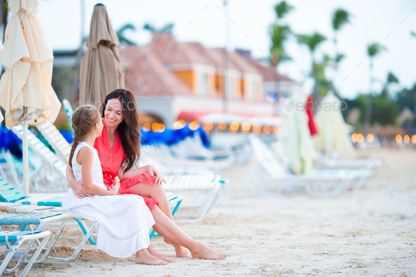 Beautiful mother and daughter at Caribbean beach enjoying summer vacation - Stock Photo - Images