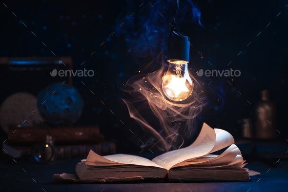 An open book with lighting by a star inside a lightbulb - Stock Photo - Images