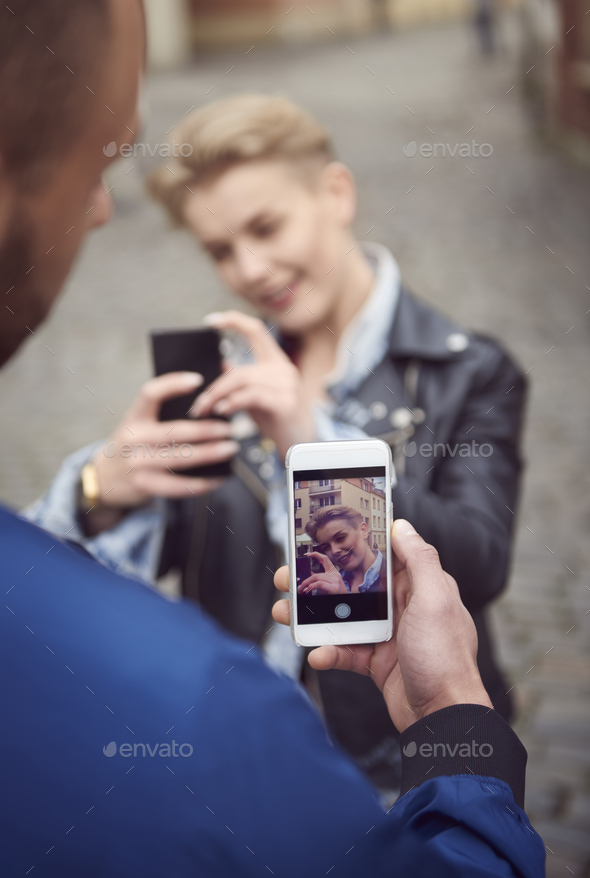 Rear view of man taking picture of his girlfriend - Stock Photo - Images