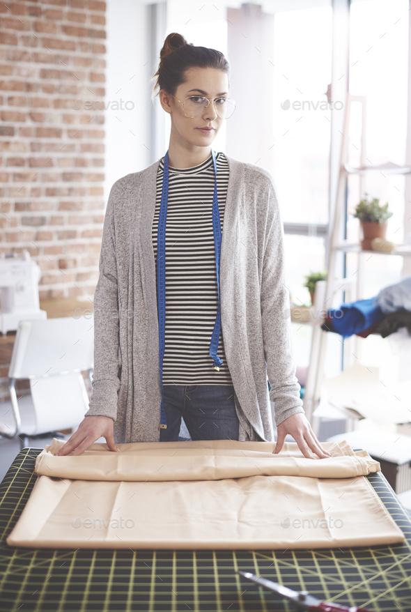 Female dressmaker measuring textile material - Stock Photo - Images