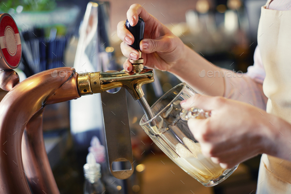 Close up of bartender pouring pint of beer - Stock Photo - Images