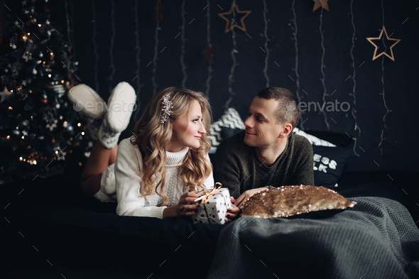 Couple on bed with Christmas present. New Year - Stock Photo - Images