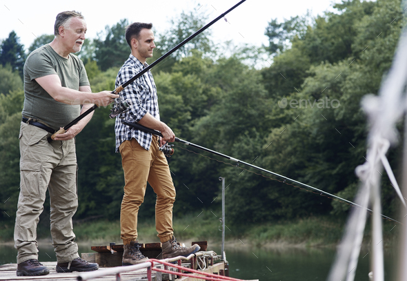 Serious male friends fishing together - Stock Photo - Images