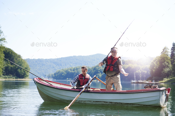 Senior man with son fishing in lake - Stock Photo - Images