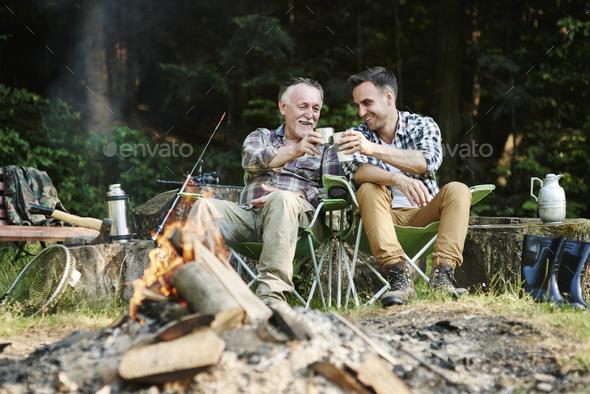 Fishermen drinking coffee beside bonfire - Stock Photo - Images