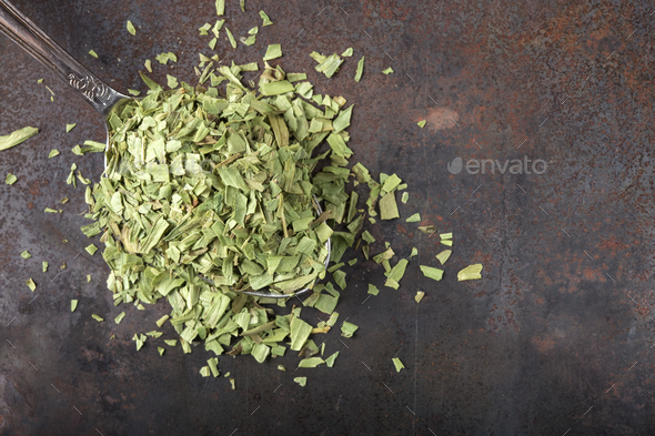 Spoon filled with dried tarragon - Stock Photo - Images