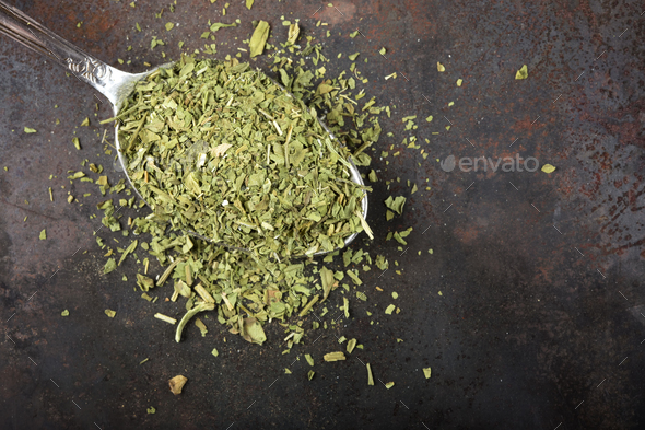Spoon filled with dried lovage - Stock Photo - Images