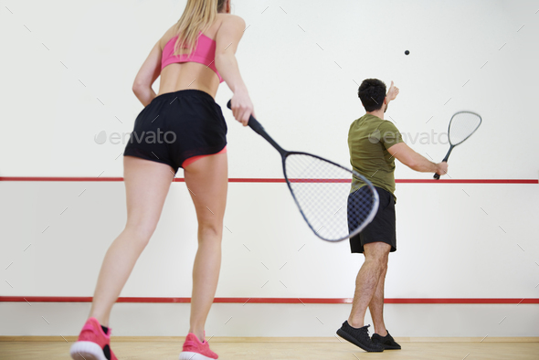 Rear view of man and woman playing squash together - Stock Photo - Images
