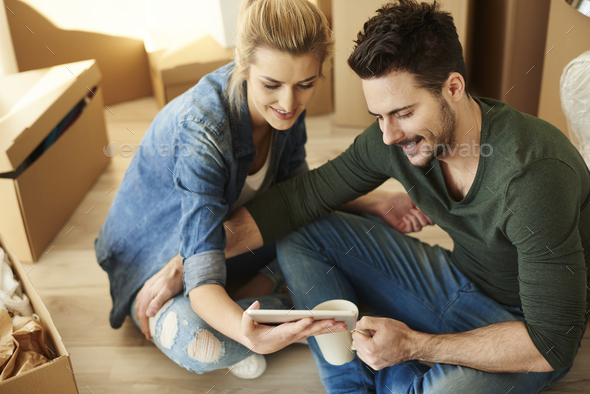 Couple around cardboard boxes with digital tablet - Stock Photo - Images