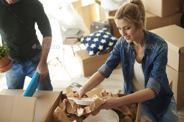 woman opening carton with porcelain things - Stock Photo - Images