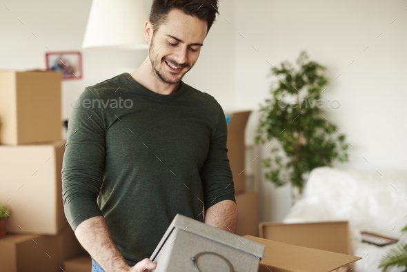 Close up of handsome man opening moving boxes - Stock Photo - Images