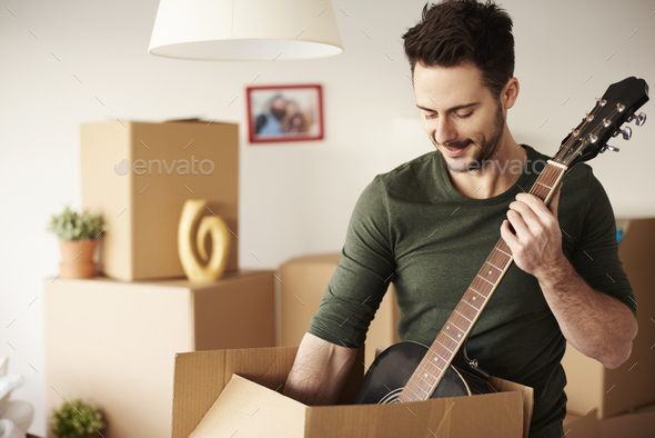 Man unpacking guitar from the cardboard box - Stock Photo - Images