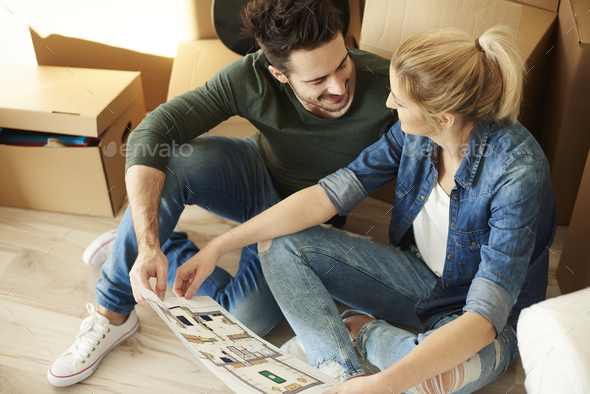 Couple sitting on the floor with blueprint - Stock Photo - Images