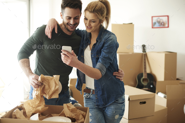 Cheerful couple using phone while moving house - Stock Photo - Images