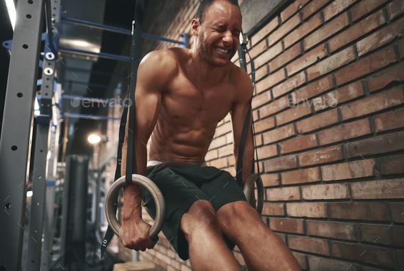 Focused man using gymnastics rings - Stock Photo - Images