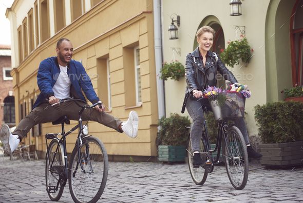 Young couple cycling with legs out - Stock Photo - Images