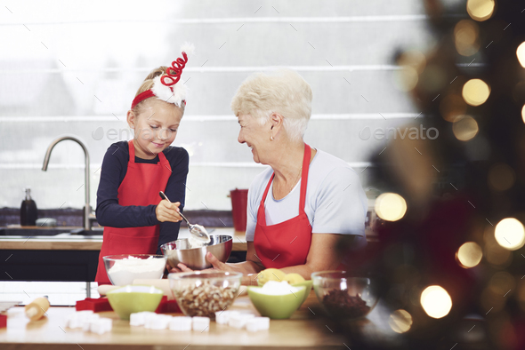 Grandmother supervising her granddaughter while cooking - Stock Photo - Images