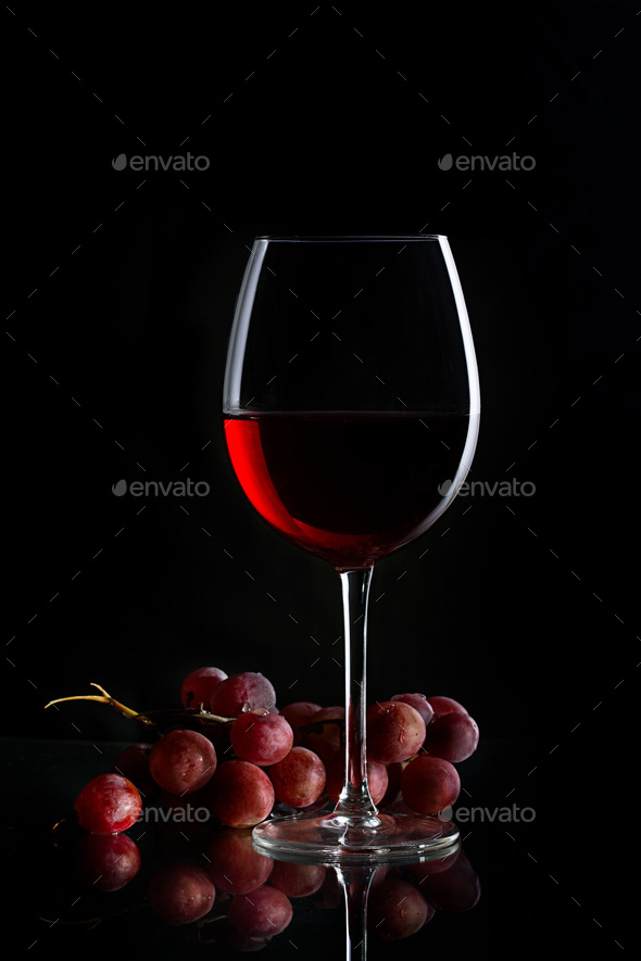 Glass of red wine and bunch of grapes on the dark background - Stock Photo - Images