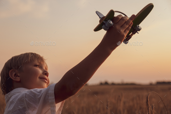 Happy child playing with a toy plane in nature during summer sun - Stock Photo - Images