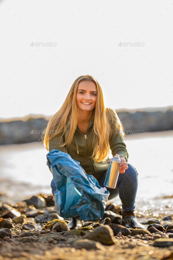 Young woman picking up aerosol can at beach - Stock Photo - Images