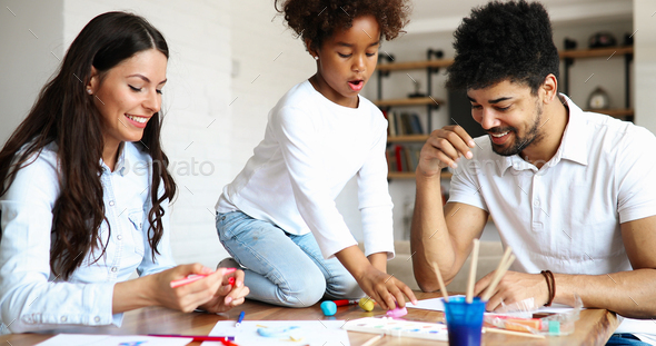 Mom and dad drawing with their daughter - Stock Photo - Images