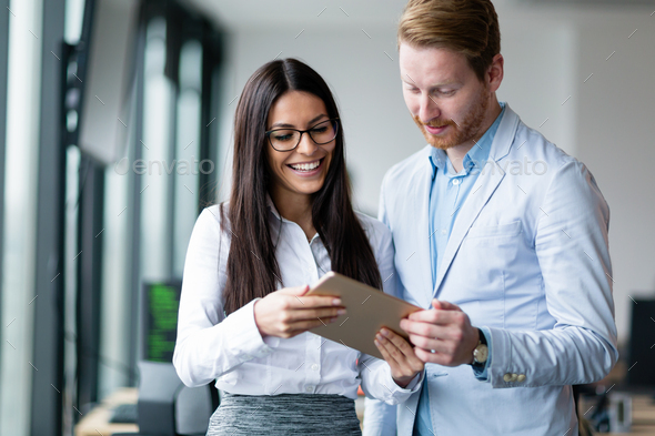 Attractive business couple using tablet in modern office - Stock Photo - Images