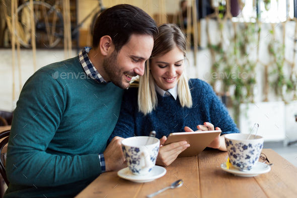 Young attractive couple using tablet in coffee shop - Stock Photo - Images