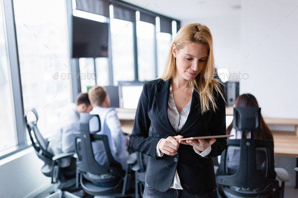 Beautiful businesswoman using digital tablet in office - Stock Photo - Images